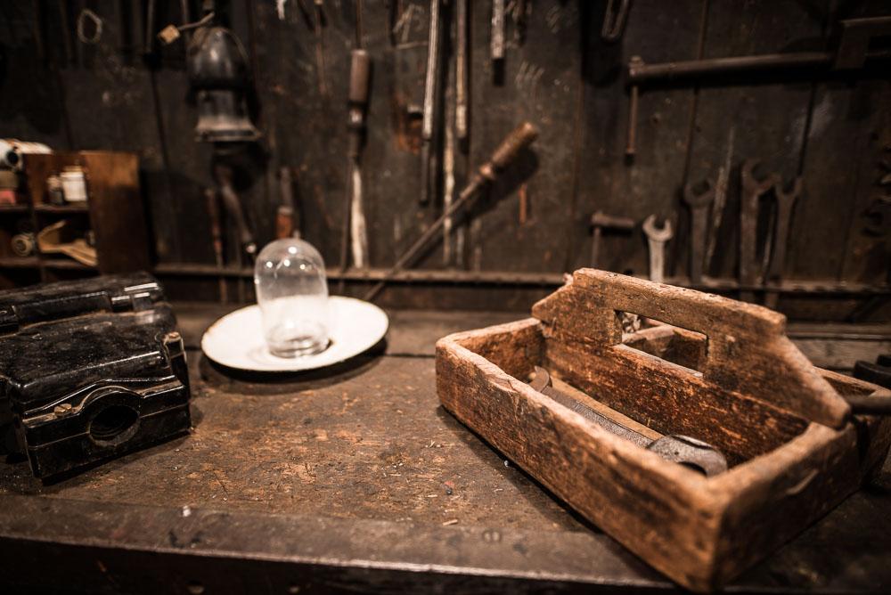 alte Werkbank mit hölzernem Werkzeugträger rechts, Glasglocke in der Mitte und einem schwarzem Block vorne links