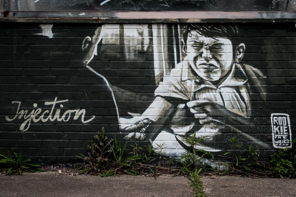 Wandgraffiti: Eine Person setzt einer anderen eine Injektion