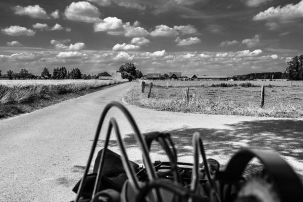 Bauerschaft, Teil vom Handbike vorne im Bild auf der Straße, viele Schäfchenwolken am Himmel, schwarz-weiß