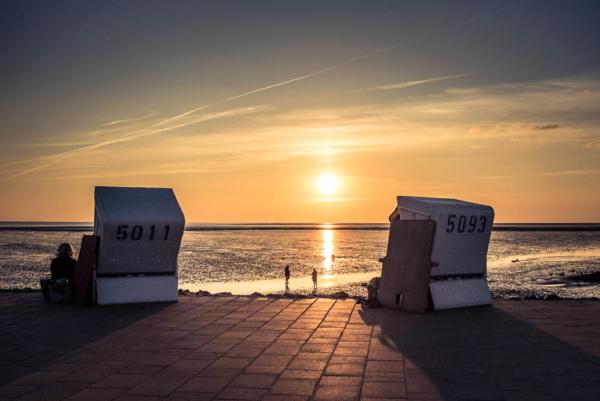 zwei Strandkörbe von hinten Blick auf die langsam untergehende Sonne