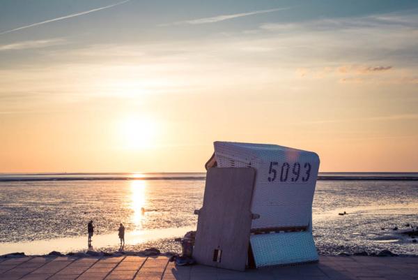 Strandkorb von hinten Blick auf die langsam untergehende Sonne
