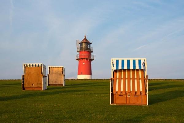 Leuchtturm Büsum im Abendlicht mit verschlossenen Strandkörben im Vordergrund