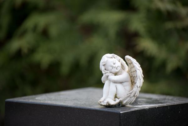 sitzender Engel auf einer Steele, grüner Blätterhintergrund unscharf